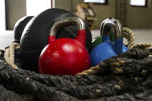 A close-up of kettle bells next to a boxing glove in a basket in a gym studio.