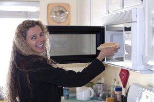Woman putting food into the microwave.