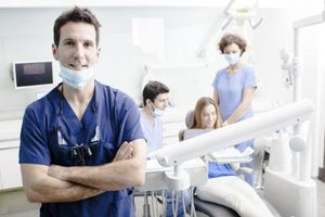 Oral surgeon standing in front of dental team in office