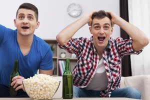 Two friends are watching a sports game on TV.