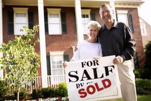 Adult couple standing in front of their home that has just been sold