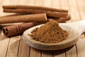 Cinnamon sticks and a spoonful of cinnamon powder.