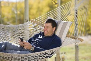 A man is sitting outside using his cell phone.