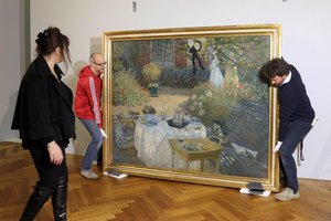 Installers hanging a Monet painting in a museum.