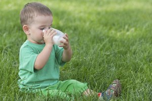 Small toddler drinking glass of soy milk.
