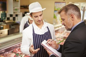 Meat inspector speaking with butcher