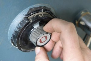 A locksmith works on a safe.