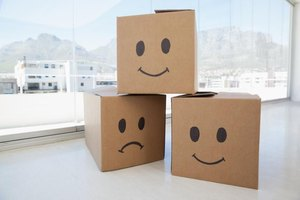 Three cardboard boxes with smiley and frowney faces on them.