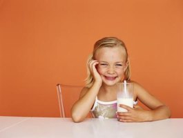 Young girl drinking a glass of milk.