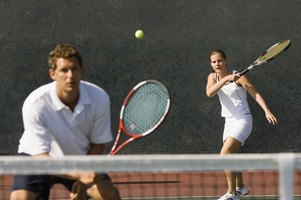 A woman hitting the ball in a game of mixed doubles.