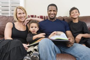 Portrait of a family reading a book together on the couch.