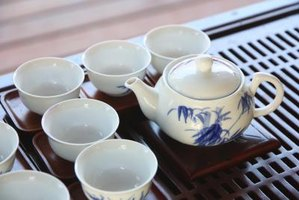 A china porcelain tea set on a wooden tray.
