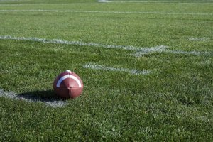 A football on the grass in a stadium.