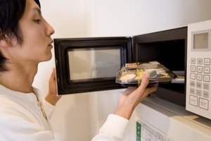 A woman is operating a microwave.