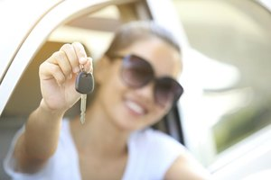 Young woman holding a key to a new car.