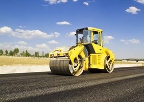 A road worker flattens a freshly paved highway.