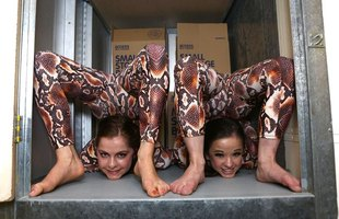 Two contortionists posing in a storage bin.