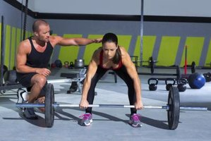 Woman lifting weights with a personal trainer.