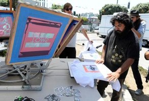 An attendee screen printing a t-shirt at a benefit.