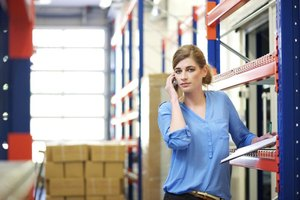 Sales supervisor on phone in warehouse.