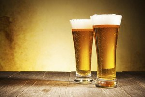 Two glasses of beer on a wood table.