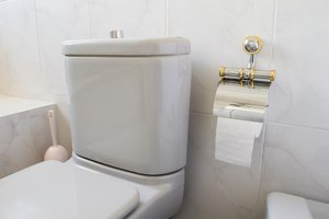 Toilet and tank in a bathroom.