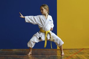 Young girl with a yellow belt strikes a pose in a karate class.