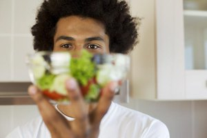 Young man holding up bowl of salad.