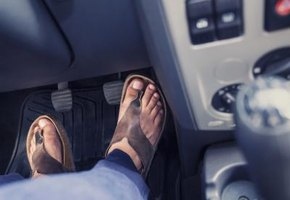 A close-up of a foot pressing down on the accelator pedal of his vehicle.