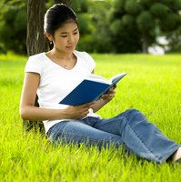 Student reading book while leaning against a tree.