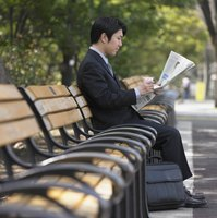 A businessman is reading a newsletter on a park bench.