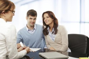 Bank lender speaking with couple about debt drawdown