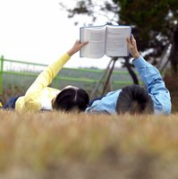 Teenagers reading book while lying in field