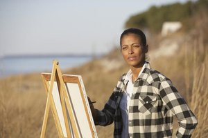 Woman painting with easel along shoreline.