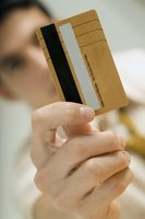 A man is holding a debt card upright.