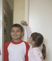 Two young kids measuring each others heights.