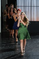 Fashion models clapping as they walk down the runway.