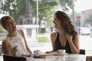 Two women laughing together at a table in public.