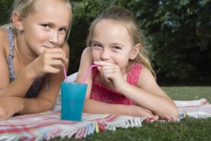 Two girls drinking from a cup with straws.