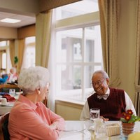Nursing home patients talking to each other during lunch.