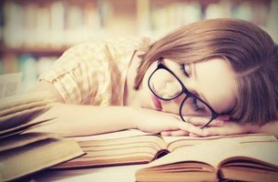 girl falling asleep on top of books