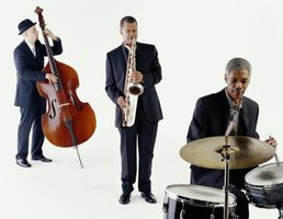 A traditional jazz trio includes a bass, a saxophone and drums