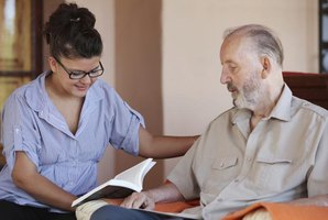 A religious social worker reads to a senior man.