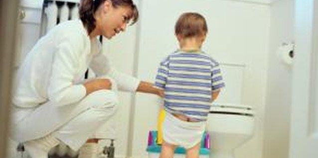 Little boys often start out sitting to pee, but a toddler urinal can help ease the transition to standing.