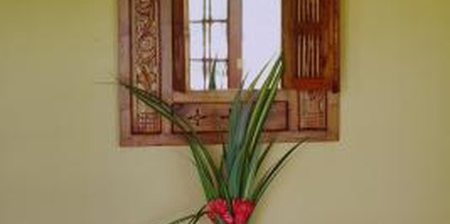A tall floral arrangement adds height and emphasis to a static, symmetrical vignette.