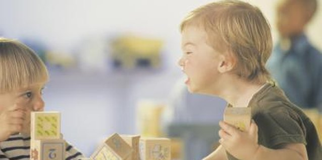 Toddlers may argue over and snatch toys such as blocks.