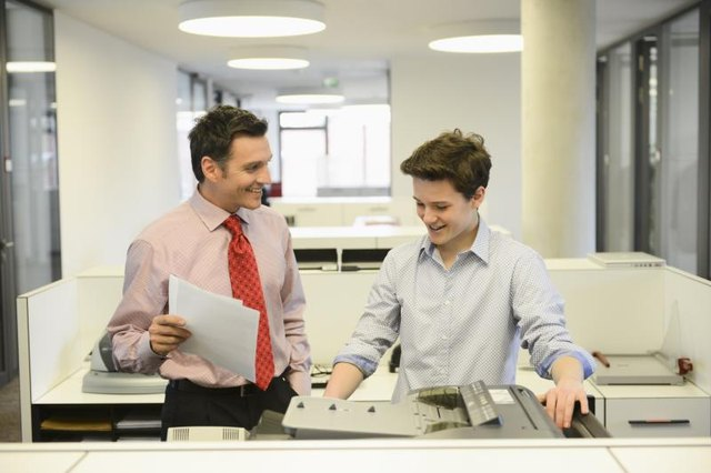 A young intern is working in a business office with a colleague.