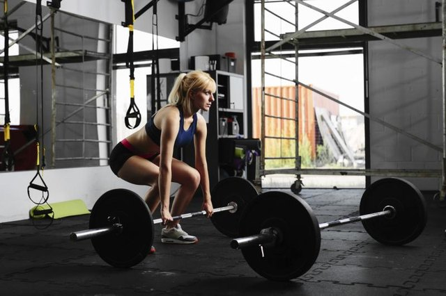 A woman performs a deadlift.
