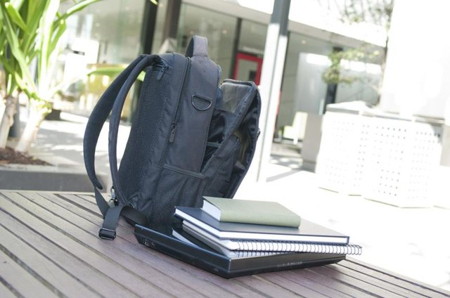 A backpack and school books on a table.