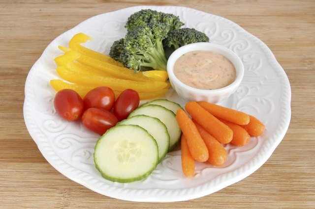 Slices of cucumber, carrot, yellow peppers, and broccoli on a plate with cherry tomatoes and a side of dressing.